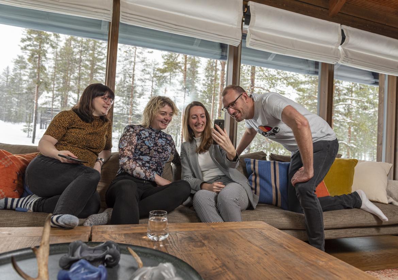 Deelnemers Fins Lapland lachen op bank