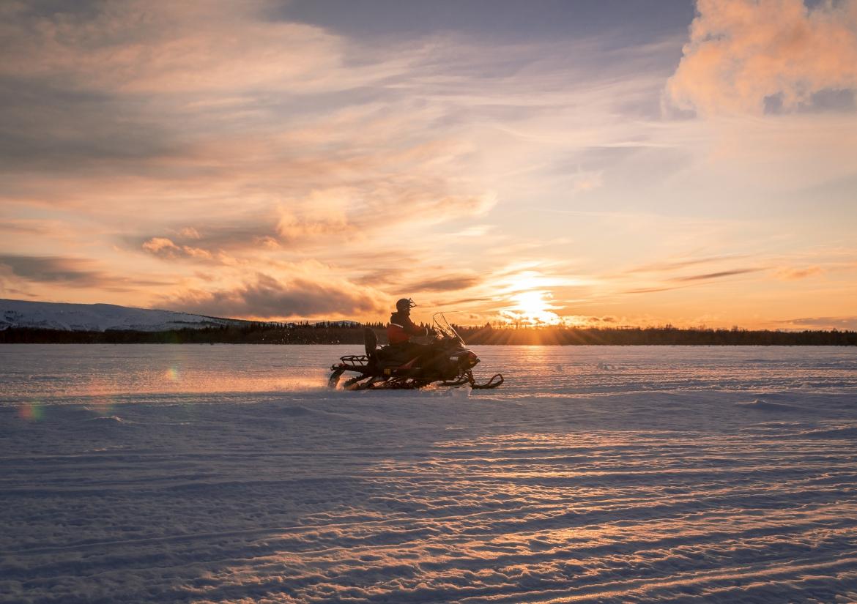 Fins Lapland sneeuwscooter in zonsondergang
